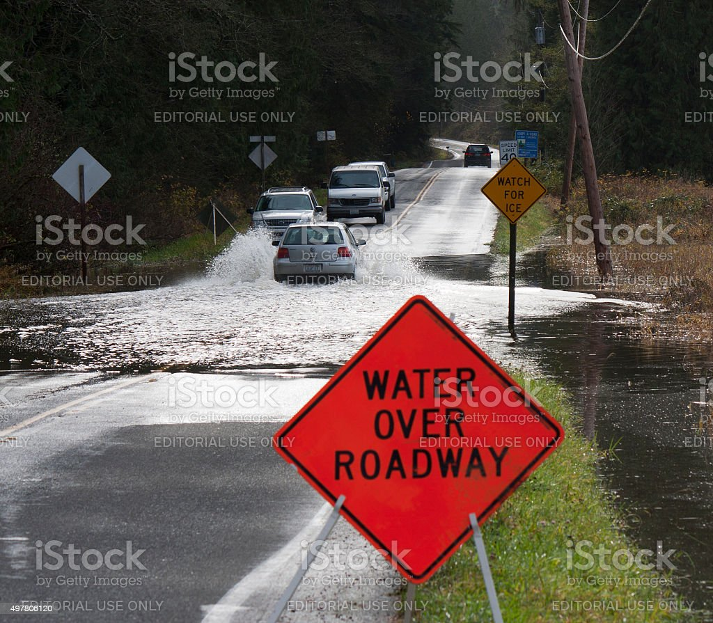 Line of Vehicles Crossing Flooded Carnation Farm Road stock photo