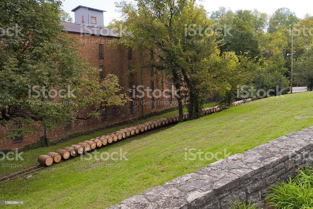 Line of whiskey barrels at distillery near warehouse royalty-free stock photo