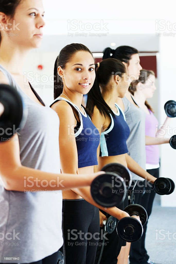 Line of young women lifting weights in gym stock photo