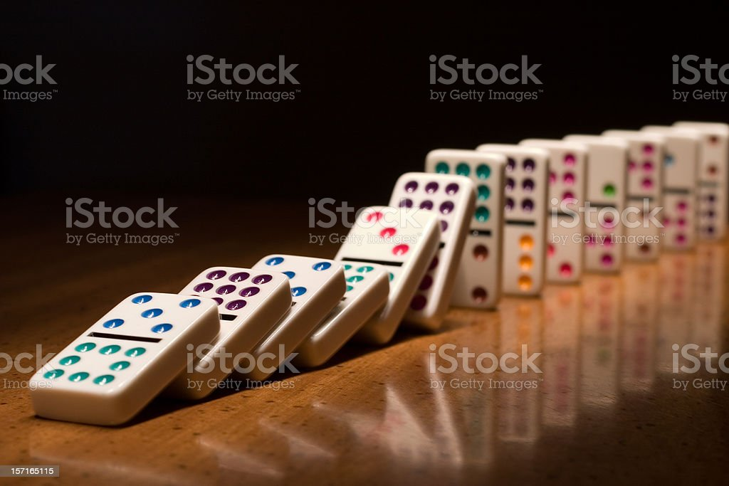 A lined up set of dominoes falling on top of one another stock photo
