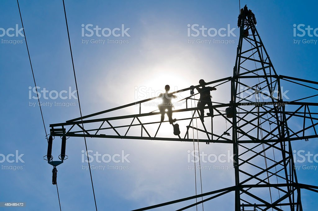 Linemen on a power pylon, bue sky and sun stock photo