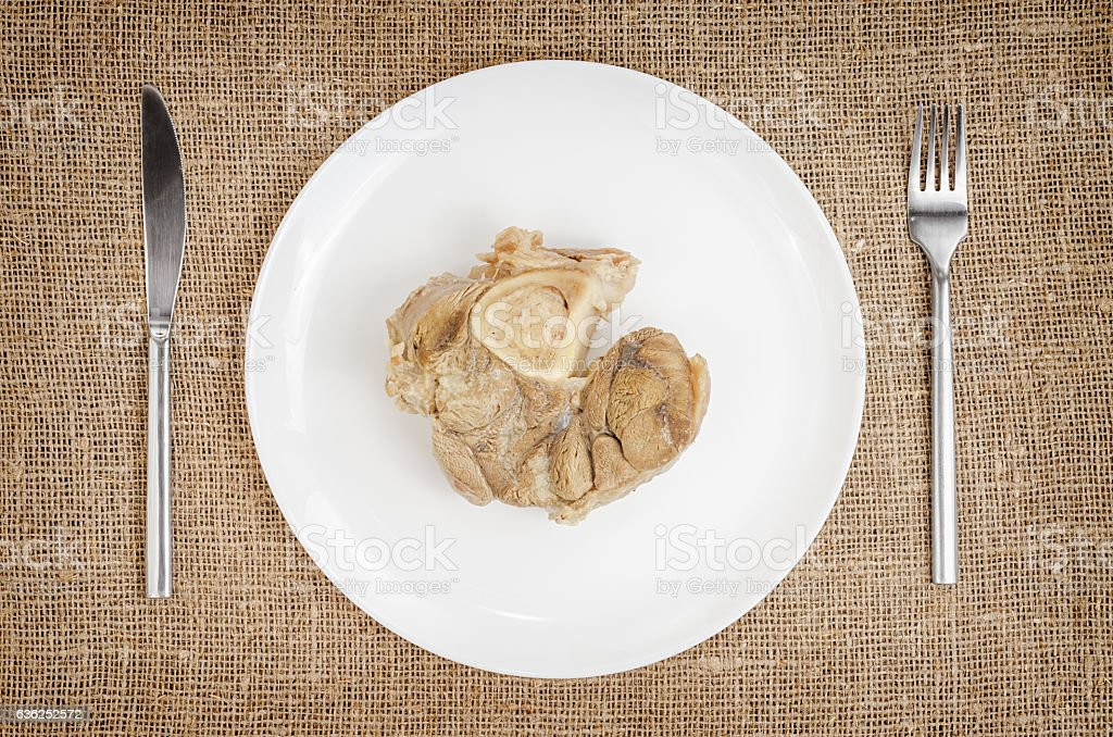 Linen background with boiled pork on plate with knife and stock photo
