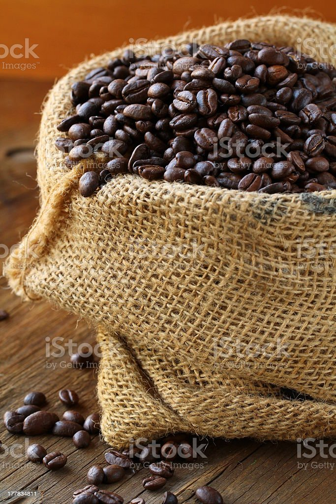 linen bag with coffee beans on wooden table royalty-free stock photo