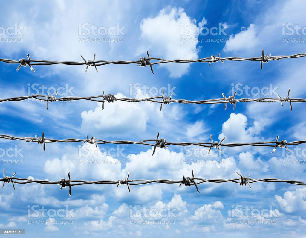 4 lines of  barbed wire, isolated against the blue sky with white clouds. stock photo
