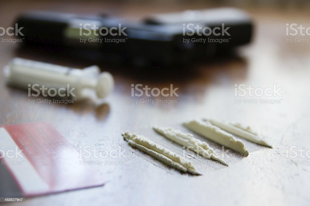Lines of cocaine,syringe,gun on the background royalty-free stock photo