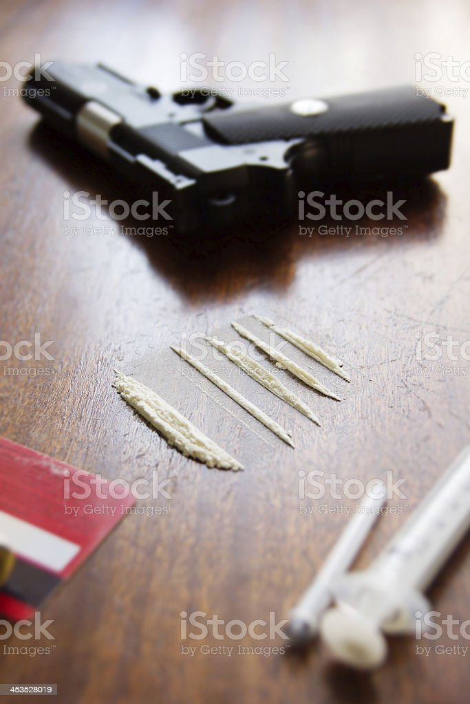 Lines of drug and a pistol on the background royalty-free stock photo
