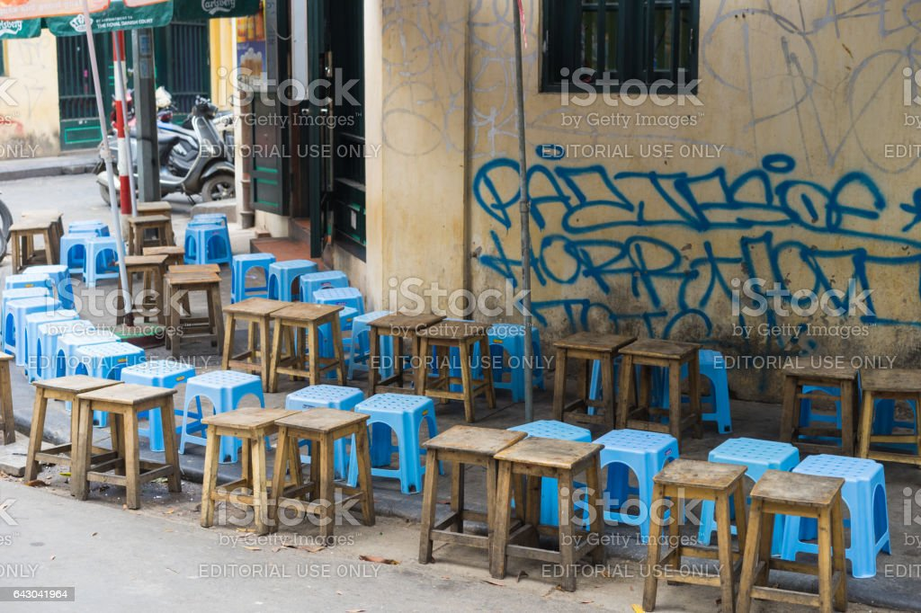 Hanoi, Vietnam - Apr 5, 2015: Lines of seats waiting for people in a coffee street stall in Luong Ngoc Quyen street. Drinking on sidewalk is typical cultural in Hanoi stock photo