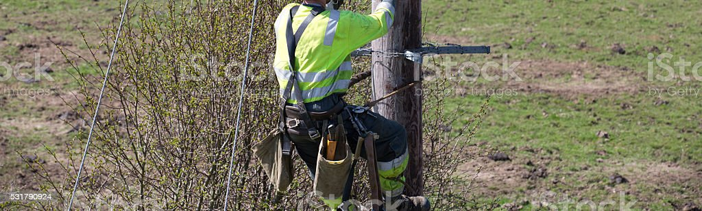 Linesman working at height harnessed on an electric power line stock photo