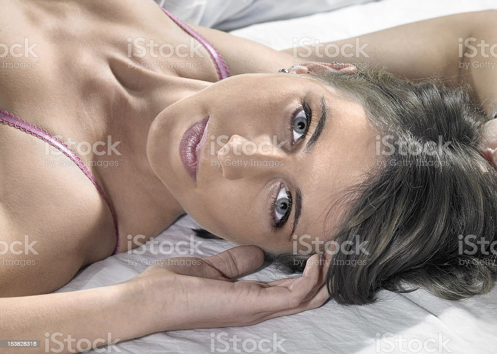 lingerie dressed lady resting on bed stock photo