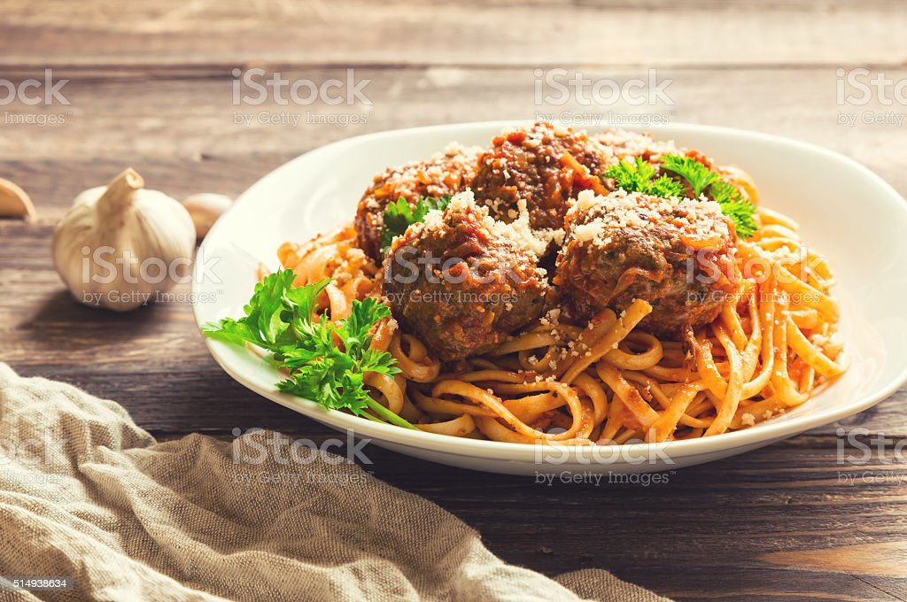 Linguine pasta with meatballs in tomato sauce and parsley stock photo