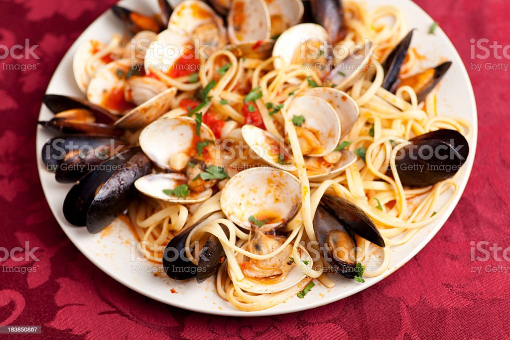 Linguini dish with mussels and clams on red table setting stock photo
