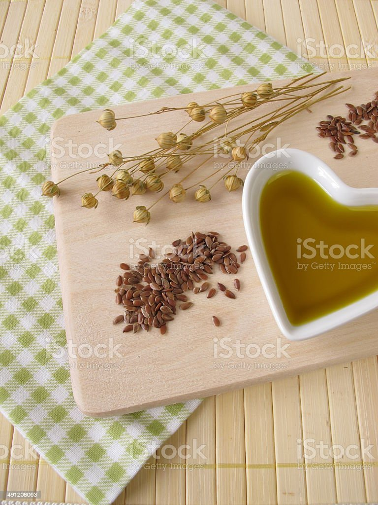 Linseed oil in a small heart-shaped porcelain bowl stock photo