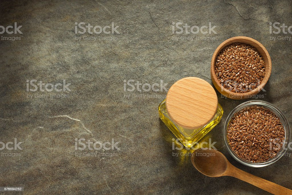 linseed oil in bottle and flax seeds on table stock photo
