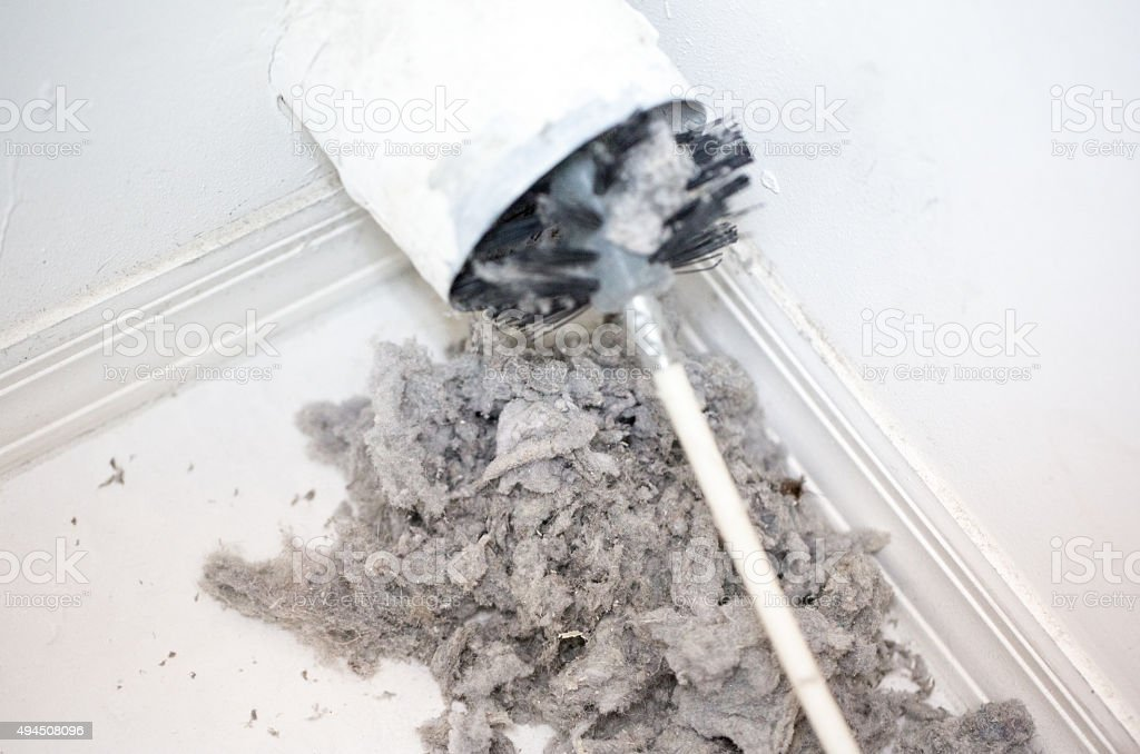 Lint being removed with a brush from a dryer vent stock photo