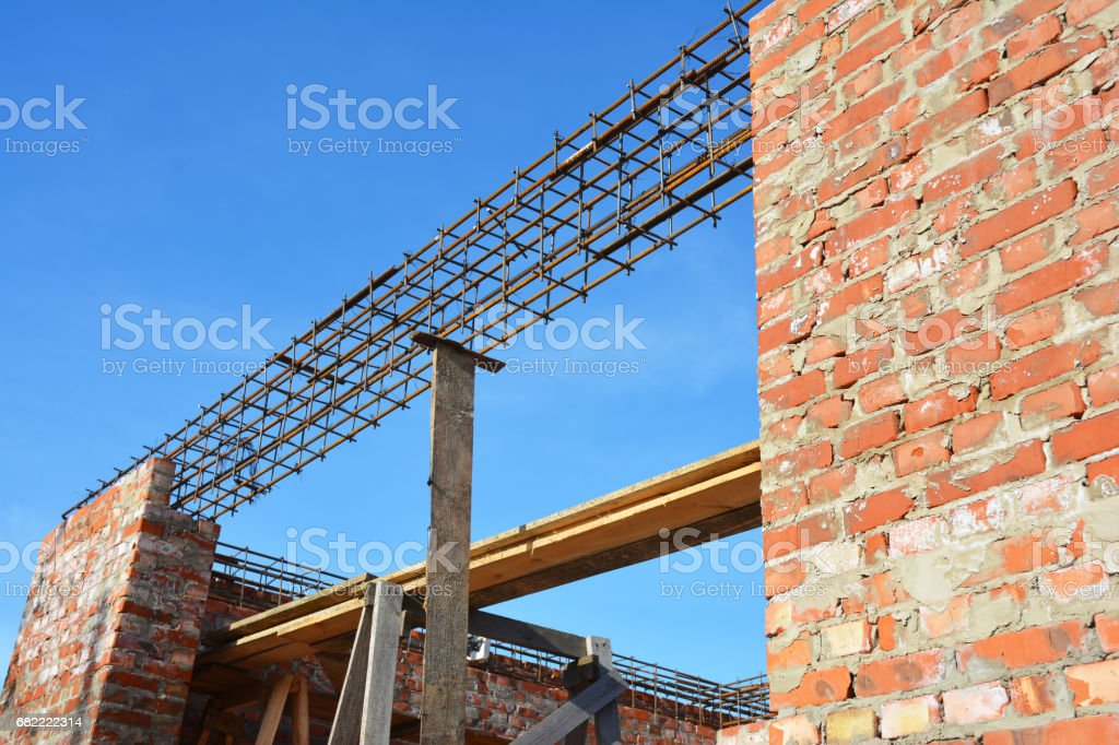 Lintel Construction. Rebar steel bars on new home construction corner, reinforcement concrete bars with wire rod as a lintel for window. Brickwork with Iron Bars for Next Floor House Construction. stock photo