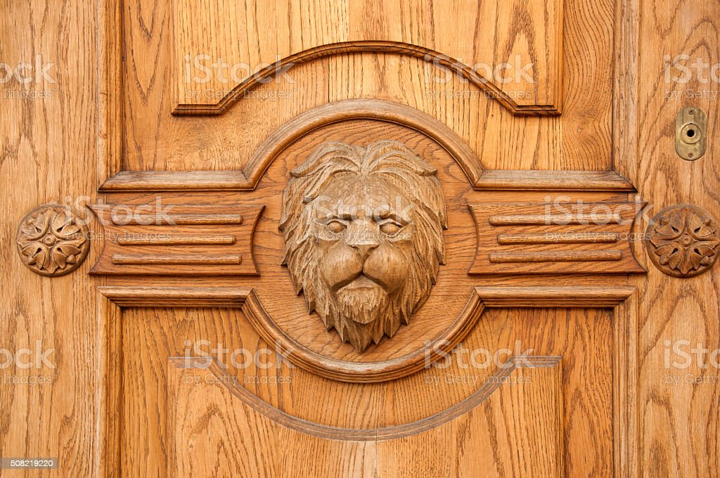 Lion fragment of an ancient carved door closeup stock photo