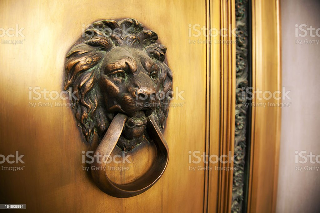 Lion Head Brass Knocker with Golden Door Frame royalty-free stock photo