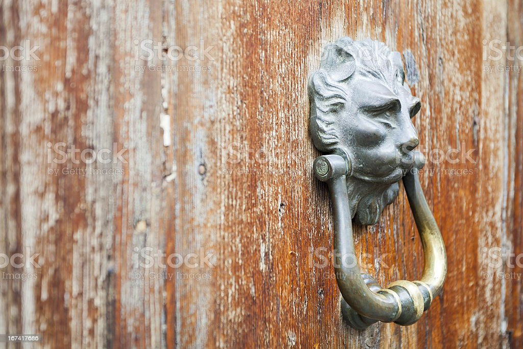 lion head shaped handle on shabby door royalty-free stock photo