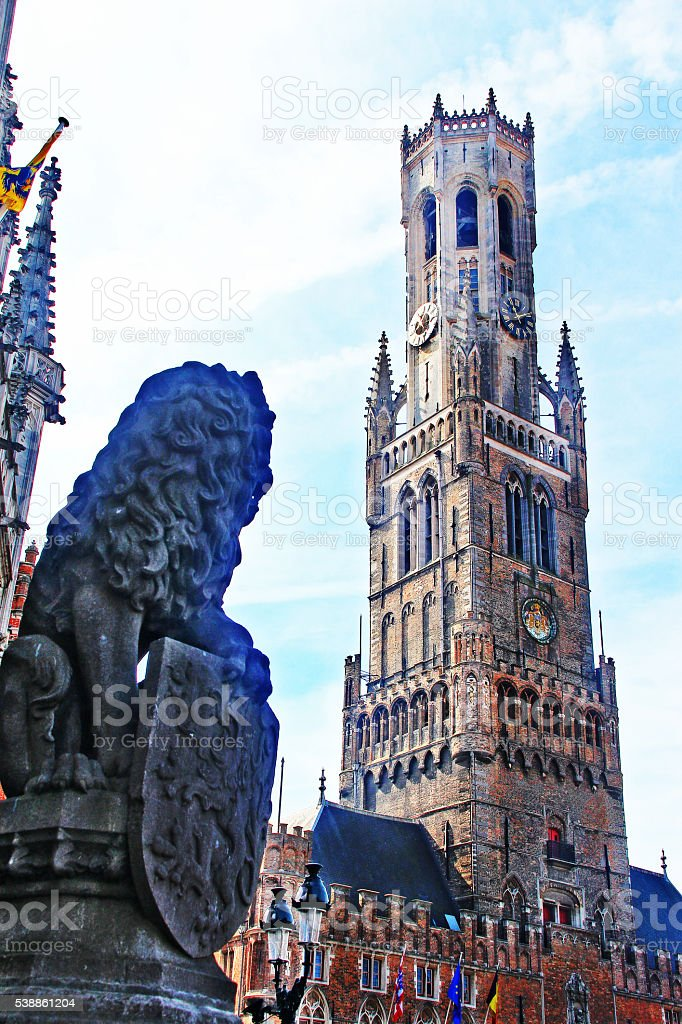 Lion statue and Belfry on Grote Markt square, Bruges, Belgium stock photo