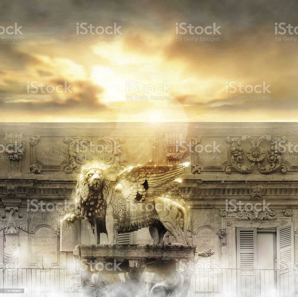 A lion statue with a fancy building and a sun in the clouds stock photo