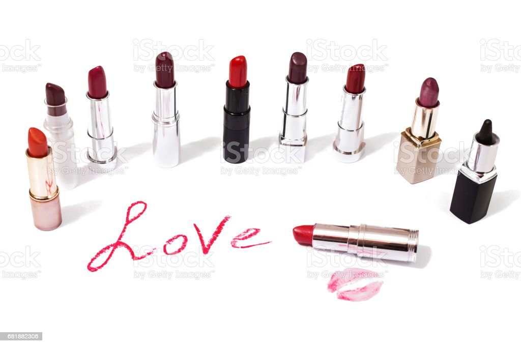 Lipstick isolated on white background. Female lip pencil. Kiss of lips on the paper. The word love written in lipstick. stock photo