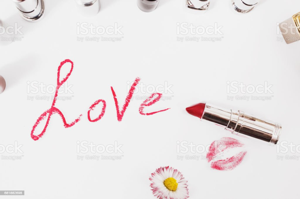 Lipstick isolated on white background. Female lip pencil. Kiss of lips on the paper. The word love written in lipstick. White flower. stock photo