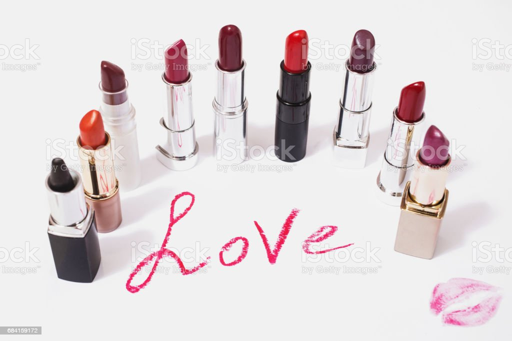 Lipstick lie on white background. Female lip pencil. Kiss of lips on paper. The word love written in lipstick. Reflection of lipstick in the mirror. View from above. Concept. Decorative cosmetics stock photo