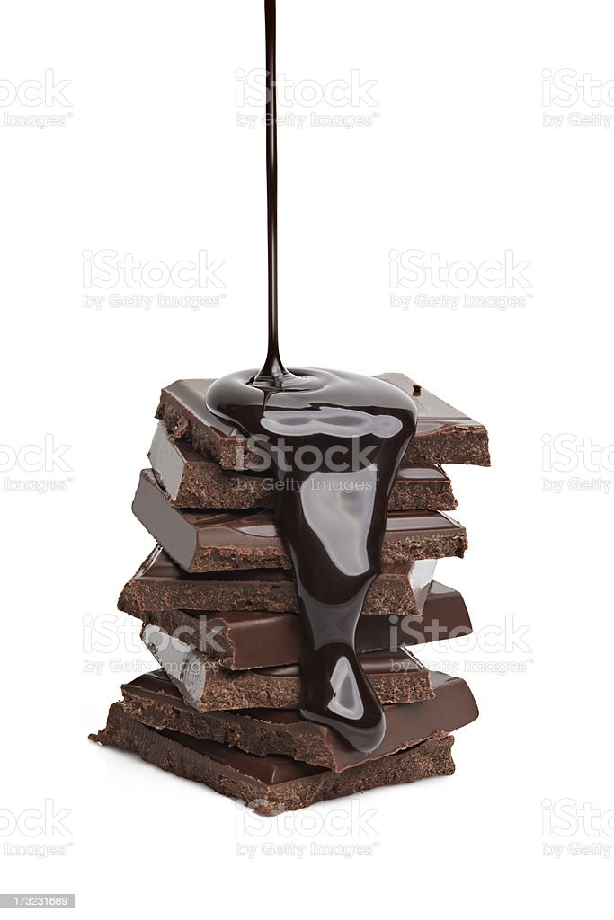 Liquid chocolate being poured on a stack of solid chocolate  stock photo