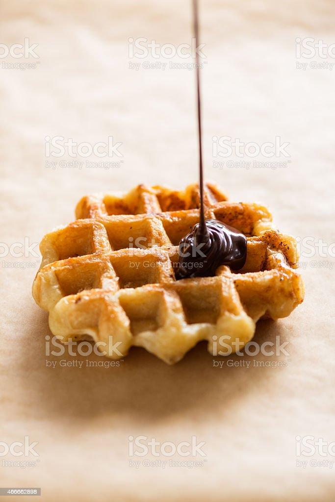 Liquid Chocolate Ganache Dripping onto Belgium Waffle, Parchment Paper Background stock photo