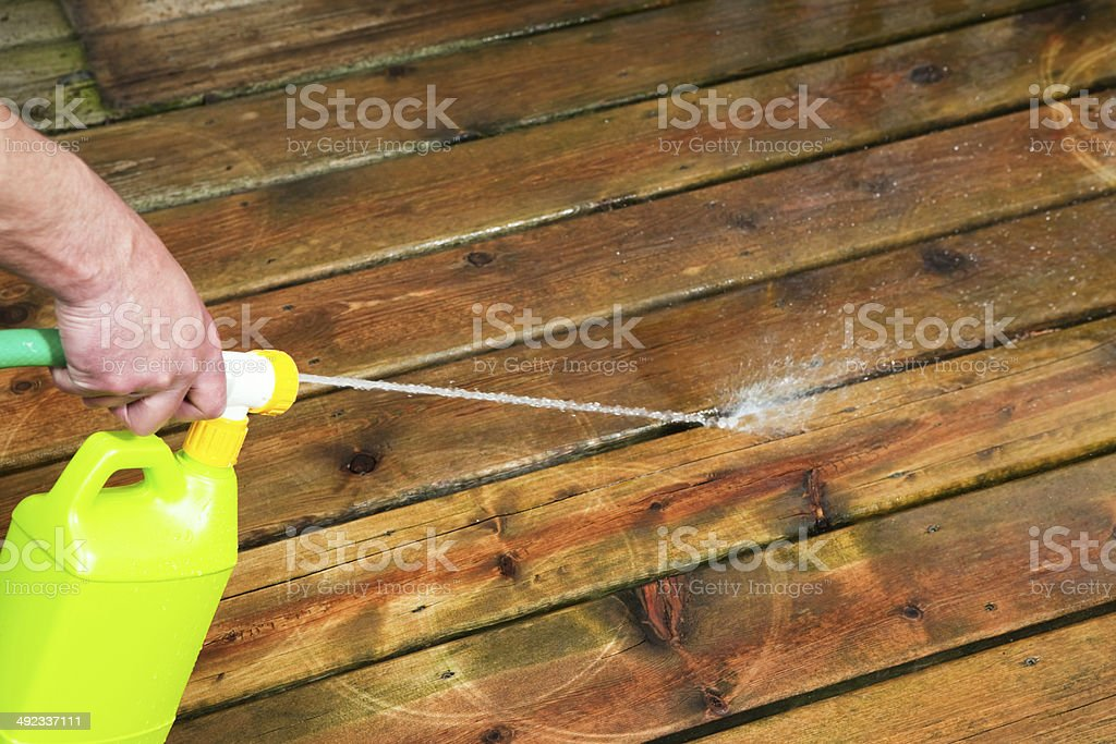 Liquid Deck Cleaner Spraying on Wood Boards royalty-free stock photo