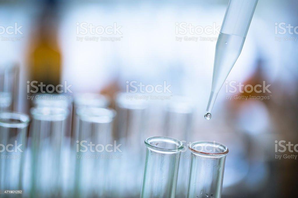 Liquid drop from laboratory glass stock photo
