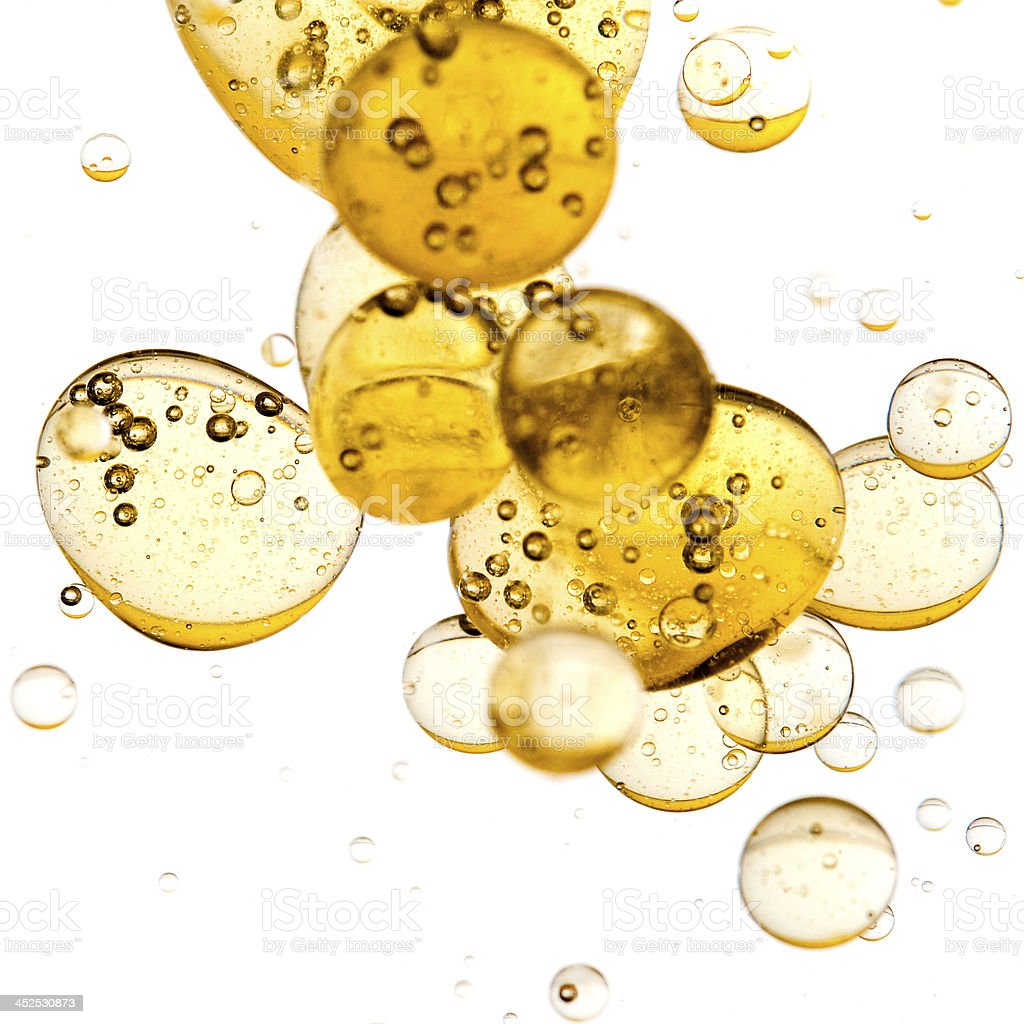 Liquid gold bubbles on white background stock photo