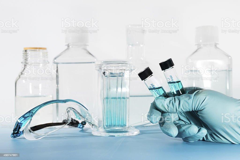 Liquid samples in gloved hand, laboratory stock photo