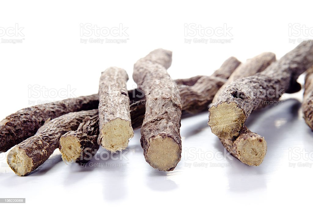 Liquorice root lying on a white surface stock photo