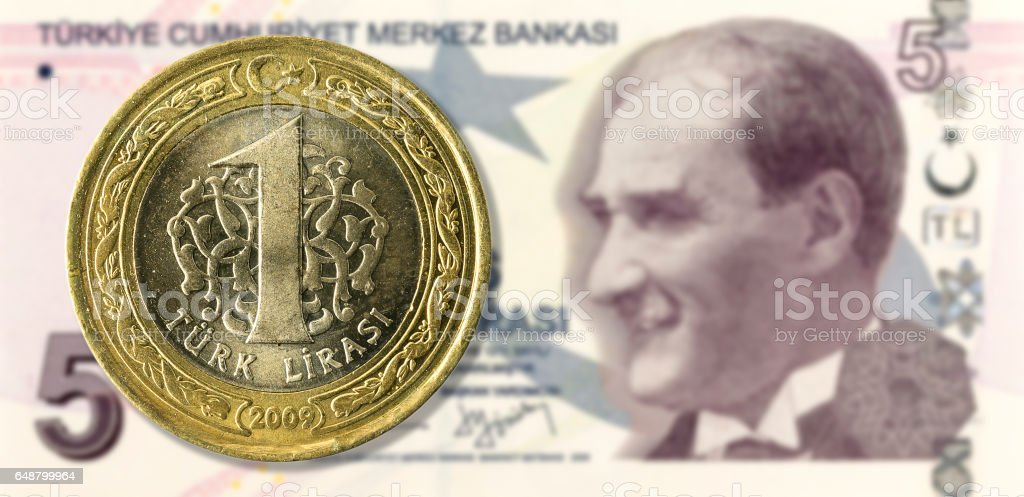 1 lira coin against 5 turkish lira bank note obverse stock photo