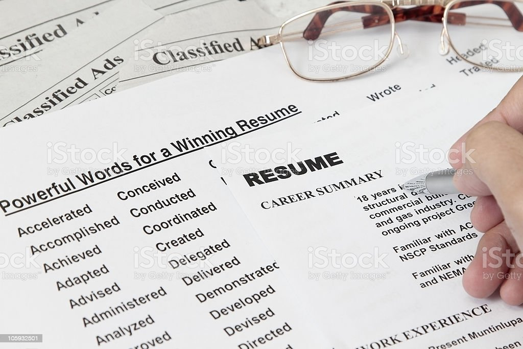 A list of words and a person writing a resume stock photo