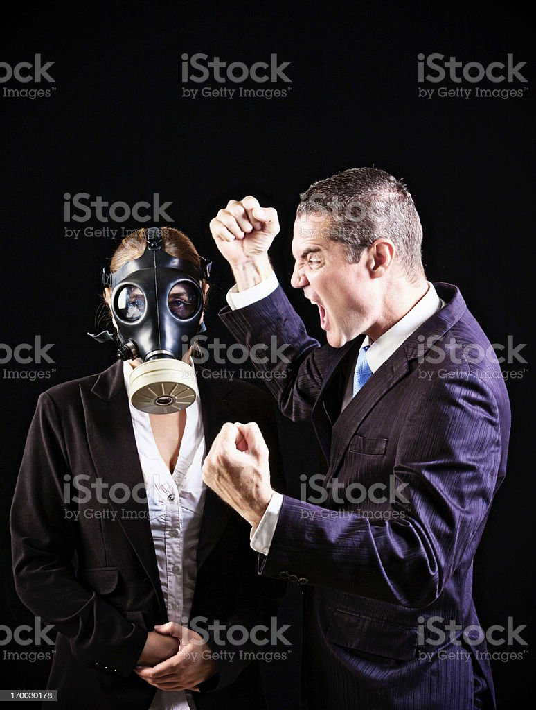 Listen to me! Furious man yelling at gas-masked woman royalty-free stock photo