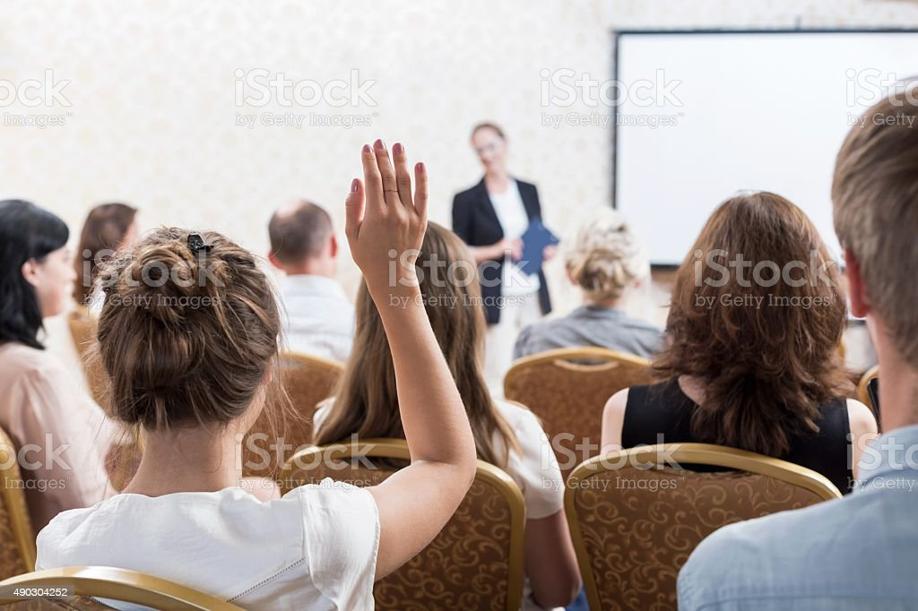 Listener raising hand to ask stock photo
