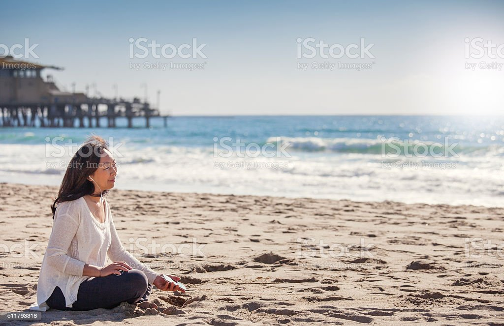 Listening to her  favorite music at the beach stock photo