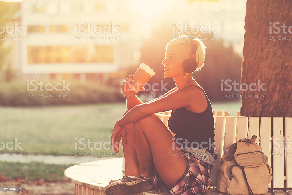 Listening to music and drinking coffee in park stock photo