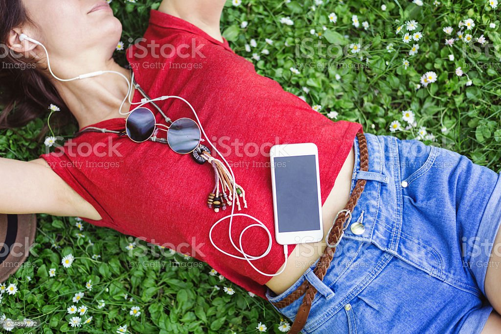 Listening to music on a meadow stock photo