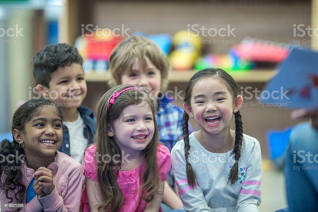 Listening to Their Teacher Read a Book stock photo