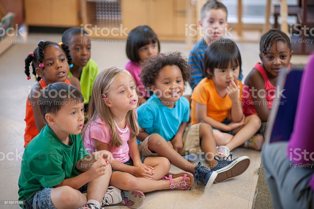 Listening to Their Teacher Read a Story stock photo