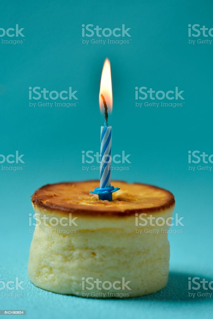 lit birthday candle on a cheesecake stock photo