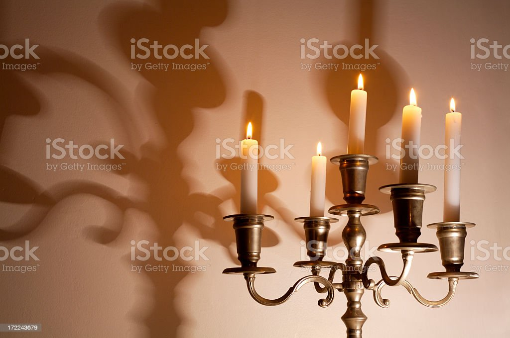 Lit candelabra with shadows on wall stock photo