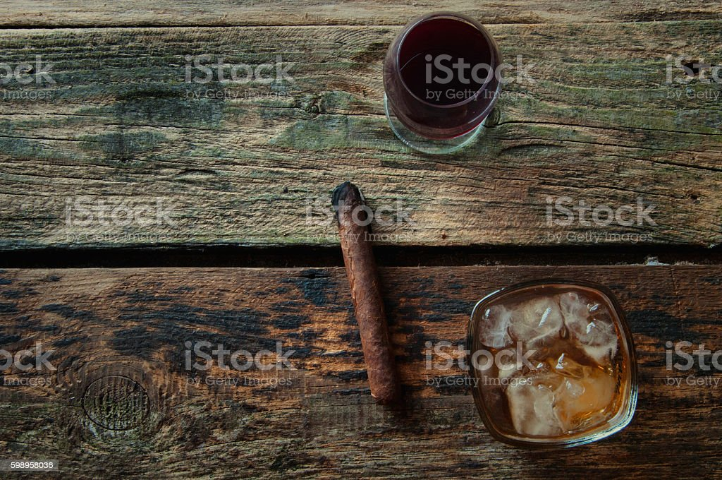 Lit cigar, wine and whiskey on a wooden background stock photo