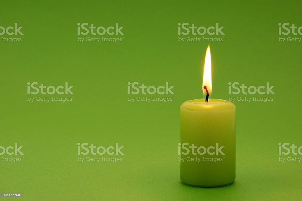 A lit green candle on a green background stock photo