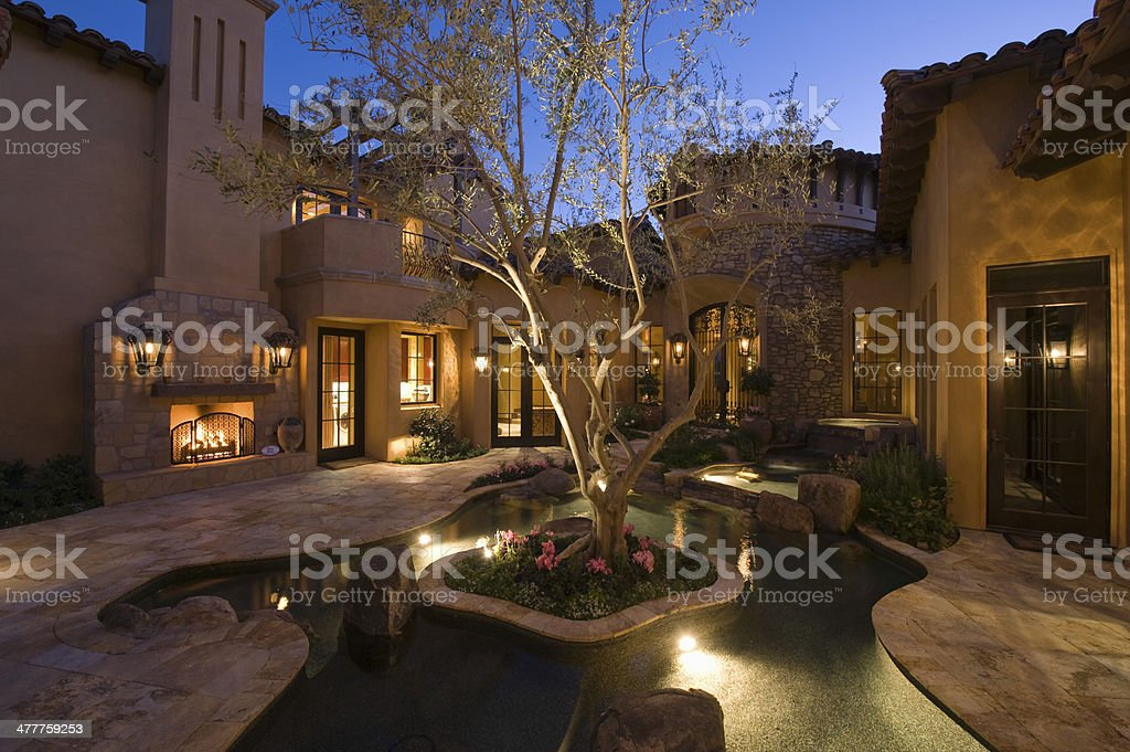 Lit House And Pond In Courtyard stock photo