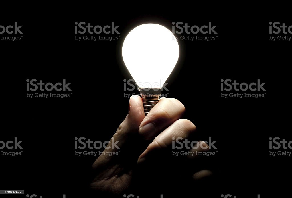 Lit lightbulb held in hand on black background royalty-free stock photo