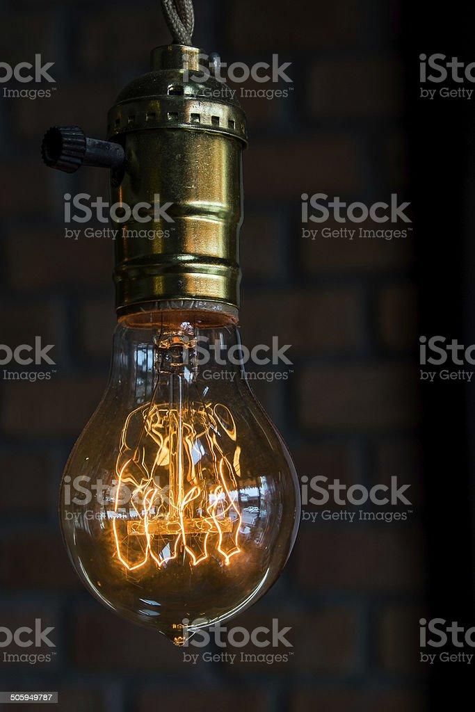 Lit Lightbulb on brick background stock photo
